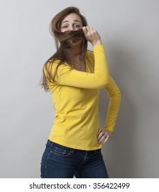 protection concept - proud young woman standing in covering her mouth with her hair for fun shyness,studio shot