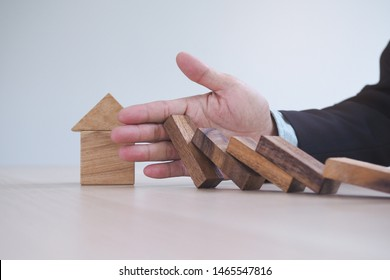 Protection finance from domino effect concept. Hands stop domino effect before destroy home.
