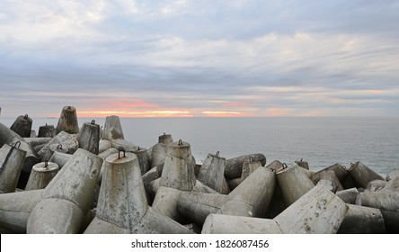 Protection of the impact of storm waves. Tetra capsules for strengthening the seashore. Breakwater on the sea coast. Concrete breakwaters. - Shutterstock ID 1826087456