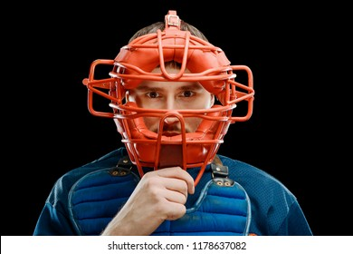 Protection mask on catcher's face. Baseball player's putting a gear on and giving a piercing look into the camera.