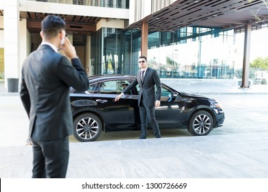 Protection officer opening car door for politician after getting an update from colleague on street