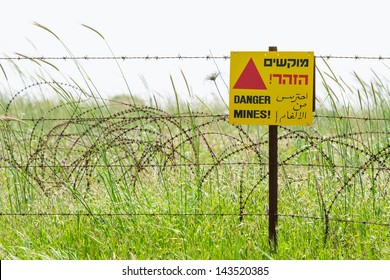 Protective barbed wire fence and warning sign around a minefield on Golan Heights