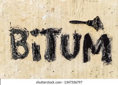 Protective bitumen mastic on concrete pavement with a brush. Bitum - black bituminous word. Construction concept.