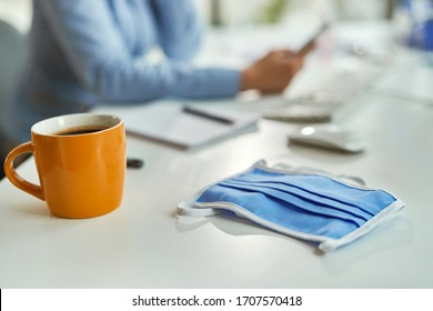 Protective cotton face mask on office desk with businesswoman in the background.