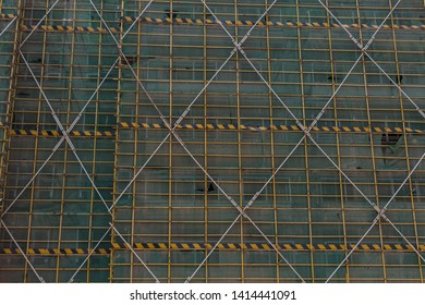 Protective fence and steel frame pattern on the exterior of the construction building