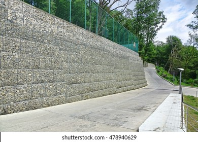 Protective Gabion Wall Filled With Raw Rocks, Stones Or Concrete Blocks And Tied With Thick Metal Wire On Landscape With Blue Sky And Trees Near The Road And Hotel Structures