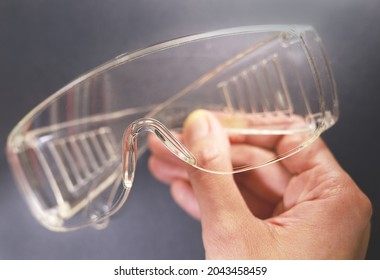 Protective glasses in hand, healthcare and safety concept. Safety glasses on black background. Personal protective equipment. Plastic goggles, transparent glasses safety at work