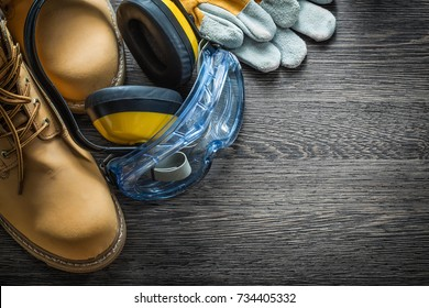 Protective gloves boots goggles earmuffs on wooden board.