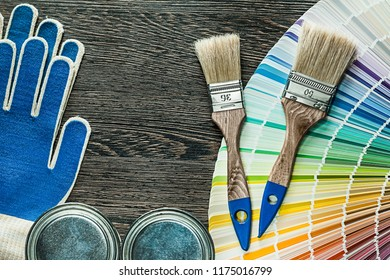 Protective gloves paint brushes cans pantone fan on wooden board.