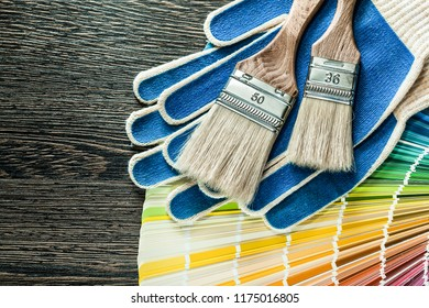 Protective gloves paint brushes pantone fan on wooden board.