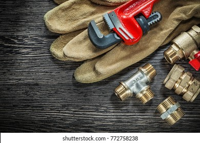 Protective gloves plumbing pipe wrench connectors water valve on wooden board.