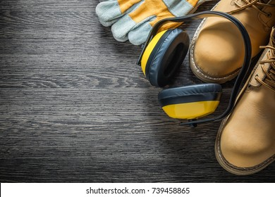 Protective gloves working boots earmuffs on wooden board.