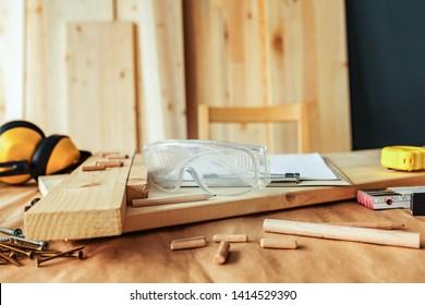 Protective goggles on carpentry woodwork workshop desk, selective focus