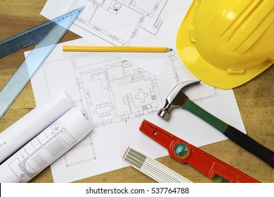 Protective helmet, mason tools and project drawings on wood background