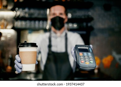 Protective mask on the face from the virus, pandemic, flu. The barista brews and sells coffee to take away. Payment via the bank's nfs terminal. Paper cup with a drink Americano, espresso, cappuccino.