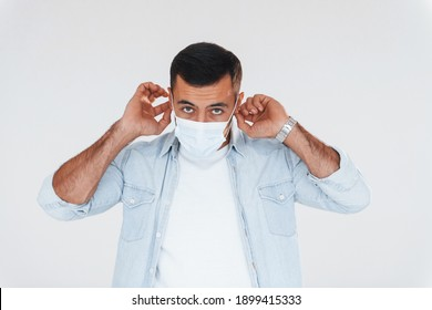 In protective mask. Young handsome man standing indoors against white background.