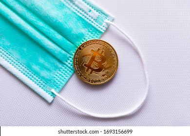 Protective medical mask and bitcoin close-up. The concept of the effect of coronavirus on cryptocurrency.