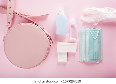 protective medical mask, sanitizer gel and gloves in pink bag. protective measures against virus, bacteria