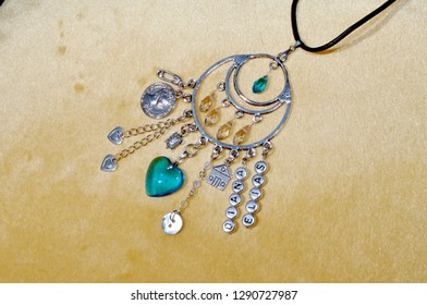 Protective power. Jewelry charm or talisman. Luck amulet on textile background. Name amulet for good luck. Silver amulet with gems and pendants. Believing in magic protecting the holder of amulet.