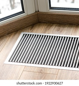 Protective radiator grille built into the floor for heating panoramic windows. Heating grid with ventilation by the floor in hardwood flooring