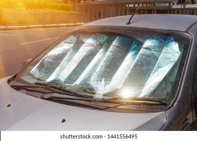 Protective reflective surface under the windshield of the passenger car parked on a hot day, heated by the sun's rays inside the car