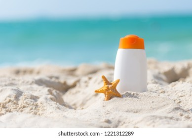 Protective sunscreen or sunblock and sunbath lotion in white plastic bottles with sandals on tropical beach, summer accessories in holiday, copy space.  Summer Concept