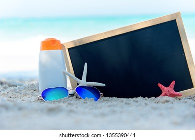 Protective sunscreen or sunblock and sunbath lotion in white plastic bottles with sandals on tropical beach.  Closeup of a chalkboard  summer  in holiday.   Summer Trips vacations Concept