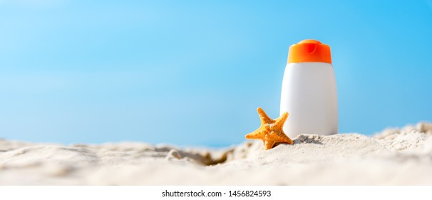 Protective sunscreen or sunblock and sunbath lotion for healthy care skin woman in white plastic bottles with starfish on tropical beach, summer accessories in holiday, copy space for text banner.
