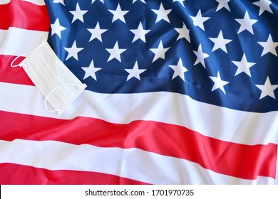 Protective surgical face mask on American national flag. Coronavirus in USA  Fllag with protective mask over to protect epidemic in America.