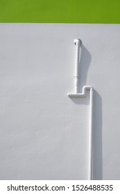 Protective white PVC corrugated pipe  with electrical cables inside on white cement wall with green stripe background outside of building in vertical frame