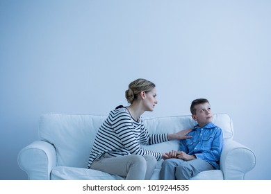 Protective woman comforting a young, autistic boy in a white room