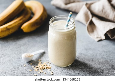 Protein banana smoothie in jar, protein scoop, oats and linen textile on table. Healthy vegan or vegetarian drink for sporty people