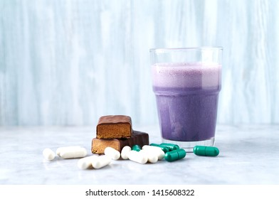 Protein bar in two pieces, Glass of Protein Shake with Milk and Blueberries, L-Carnitine and Beta-alanine capsules in background. Concept for Sport nutrition. Copy space.