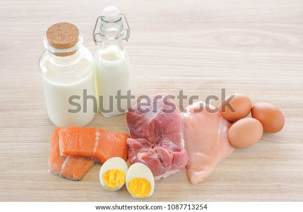 Protein diet and healthy food concept : raw meat, chicken, salmon fish, milk and eggs on wooden table background