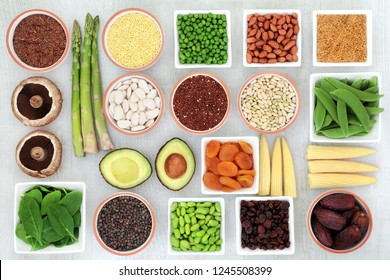 Protein plant health food selection for a healthy diet with grain, legumes, dried fruit, seeds, nuts and vegetables on rustic wood background. Foods high in fibre, antioxidants, vitamins and minerals.
