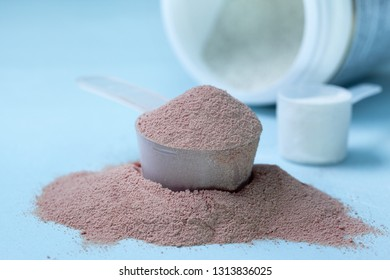 protein powder with chocolate on a blue background close up