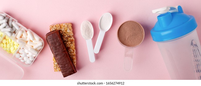 Protein powder, scoop, energetic musli bars, vitamin pills, gainer, shaker on pink background - concept of sport diet, healthcare, nutrition fit fitness food, copyspace
