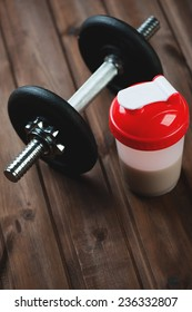 Protein shake with a dumbbell, high angle view, vertical shot