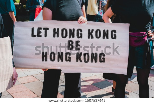 Protest in Hong Kong. Protestor holds a cardboard with an inscription: Let Hong Kong Be Hong Kong. Fight for democracy
