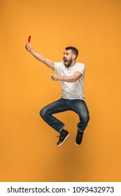 Protest - red card to the football referee. The young jumping man as football supporter with red card on orange background. Support concept. Human emotions, facial expression, soccer, football, sport
