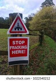 A protest sign says stop fracking here and is nailed to a rustic wooden fence in rural English countryside in the Surrey Hills North Downs