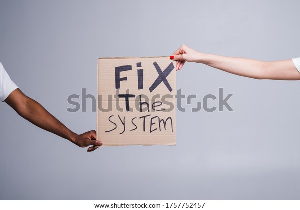 protest white and black hands holding cardboard poster with message text FIX THE SYSTEM isolated on white background.