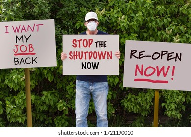 Protester with cap and medical protection mask demonstrate against stay-at-home orders due to the COVID-19 pandemic with sign saying Stop the Shutdown Now. More sign boards around him.