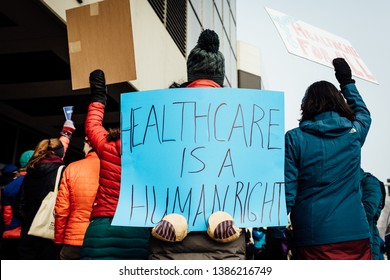Protester in a crowd holds a sign that says healthcare is a human right