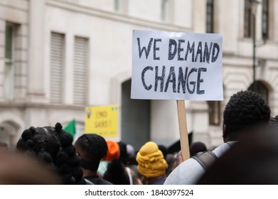 Protester holding a 'WE DEMAND CHANGE' placard