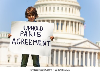 Protester holding sign uphold Paris agreement in hands
