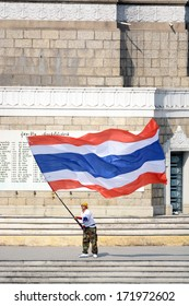 """Protester waving Thai flag to protest against the government corruption in  """"Shut down Bangkok"""" campaign. on January 18,2014 in BANGKOK,THAILAND."""