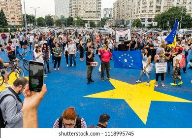 Protesters banners/People holding banners with messages against corruption, the government and the current party in power over an EU star on the pavement. Bucharest, Romania, June 21, 2018.