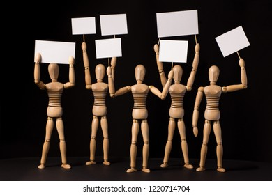 Protesters wooden puppets with white posters or banners in their hands on a black background