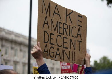 A protestor holds a political banner with make america decent again message
